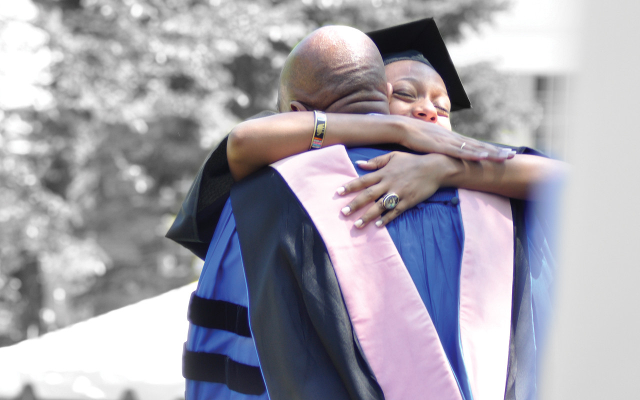 College graduate hugging professor or staff member